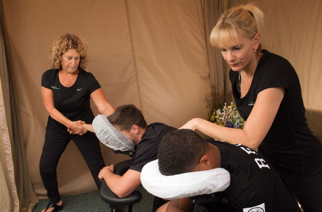 San Diego Chair Massage, two massage therapists woring on two different men in massage chairs